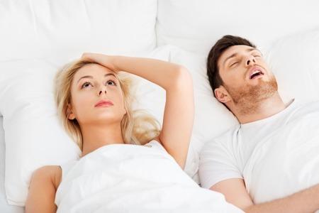 Foto de sleeping problems and people concept - unhappy woman lying in bed with snoring man - Imagen libre de derechos