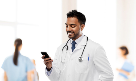 Foto de smiling indian male doctor with smartphone - Imagen libre de derechos