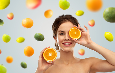 Foto de smiling woman with oranges over fruits background - Imagen libre de derechos