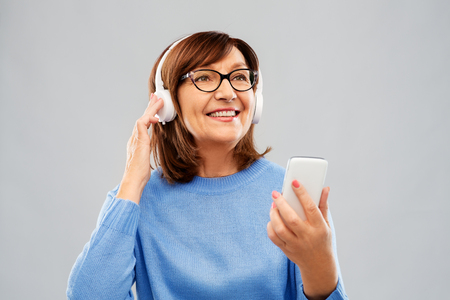 Photo for senior woman in headphones listening music on cell - Royalty Free Image