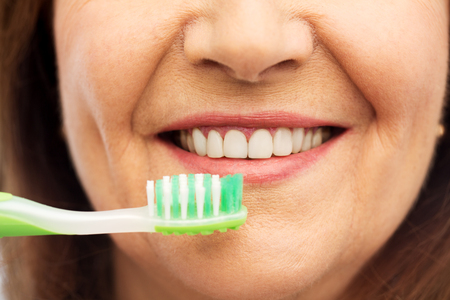 Photo pour senior woman with toothbrush brushing her teeth - image libre de droit