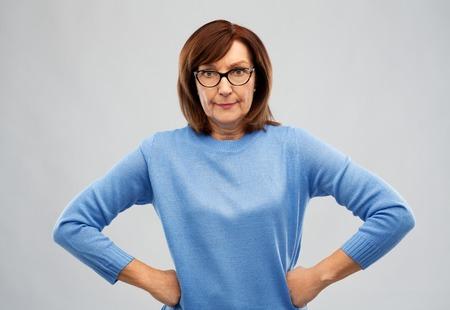 Foto de angry senior woman in glasses over grey background - Imagen libre de derechos