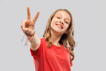 Photo for smiling teenage girl in red t-shirt showing peace - Royalty Free Image