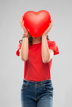 Photo for teenage girl with red heart shaped balloon - Royalty Free Image