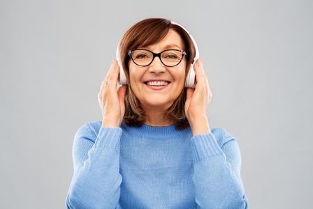 Photo pour senior woman in headphones listening to music - image libre de droit