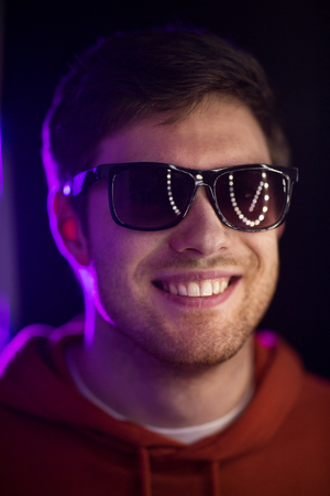Photo pour leisure, clubbing and nightlife concept - portrait of smiling young man in sunglasses at dark room over ultra violet neon lights of night club - image libre de droit