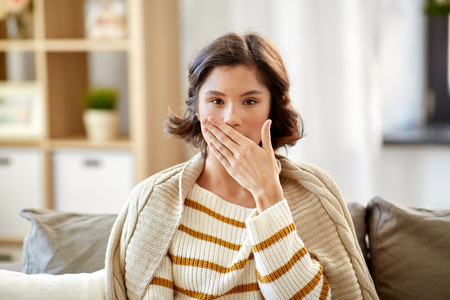 Foto de sick woman in blanket coughing at home - Imagen libre de derechos