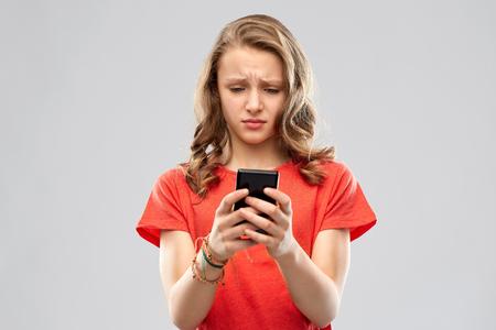 Foto de sad teenage girl using smartphone - Imagen libre de derechos