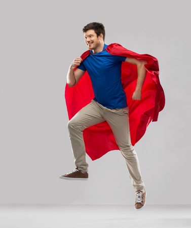 Photo for man in red superhero cape jumping in air - Royalty Free Image
