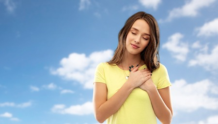 Photo pour appreciation, valentine's day and sincere emotions concept - thankful young woman or teenage girl with closed eyes in yellow t-shirt holding hands on chest or heart over blue sky and clouds background - image libre de droit