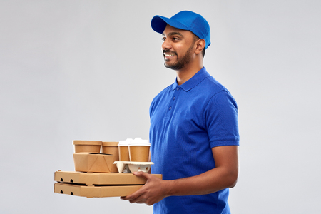 Photo pour happy indian delivery man with food and drinks - image libre de droit