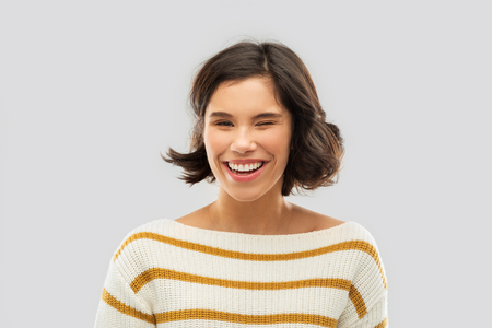 Foto de happy smiling woman in striped pullover winking - Imagen libre de derechos