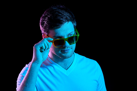 Photo pour man in sunglasses over ultra violet neon lights - image libre de droit