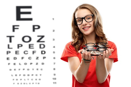 Foto de teenage girl holding glasses over eye test chart - Imagen libre de derechos