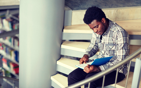 Photo pour African student boy or man reading book at library - image libre de droit