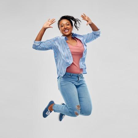 Foto de Happy African American woman jumping high - Imagen libre de derechos