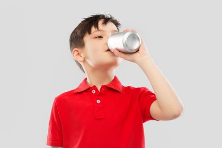Foto de boy in red t-shirt drinking soda from tin can - Imagen libre de derechos