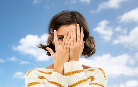Photo for people concept - young woman in striped pullover closing face with hands and looking by one eye through her fingers over blue sky and clouds background - Royalty Free Image