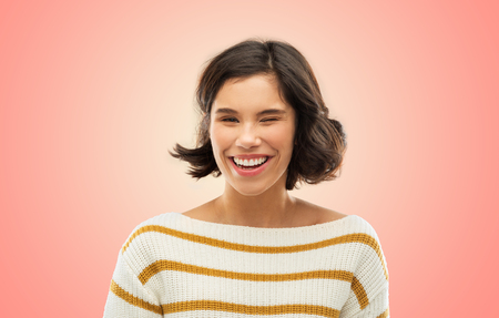 Foto de expression and people concept - happy smiling young woman in striped pullover winking over living coral background - Imagen libre de derechos