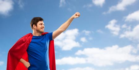Foto de A man in red superhero cape over sky background - Imagen libre de derechos