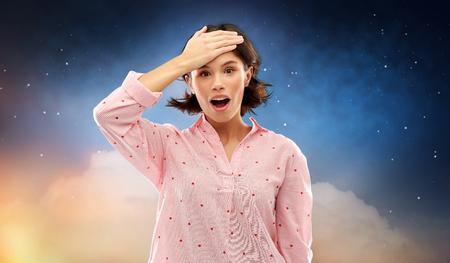 Photo pour Confused young woman in pajama over night sky - image libre de droit