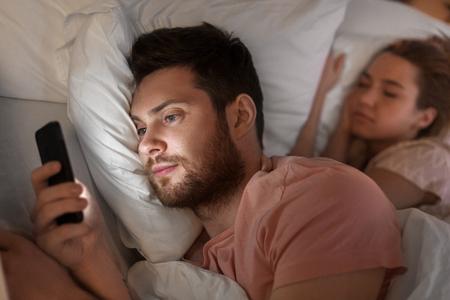 Foto de man using smartphone while girlfriend is sleeping - Imagen libre de derechos