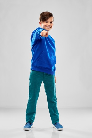 Photo pour smiling boy in blue hoodier pointing finger - image libre de droit