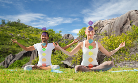 Photo for mindfulness, spirituality and outdoor yoga - couple meditating in lotus pose with seven chakra symbols over seychelles nature background - Royalty Free Image