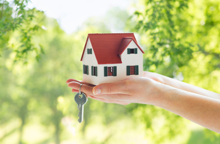 Foto de mortgage, real estate and property concept - close up of hands holding house model and home keys over green natural background - Imagen libre de derechos