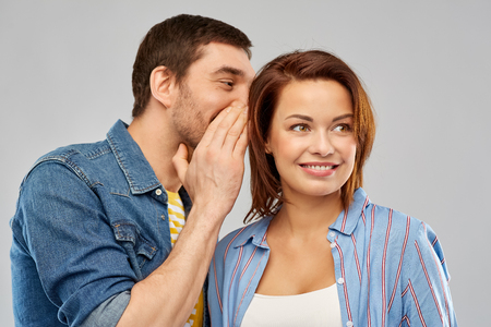 Photo for happy couple whispering over grey background - Royalty Free Image