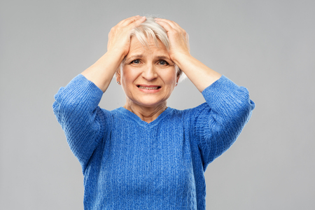 Foto de Stress, emotions and old people concept - portrait of stressed senior woman in blue sweater holding to her head over grey background - Imagen libre de derechos