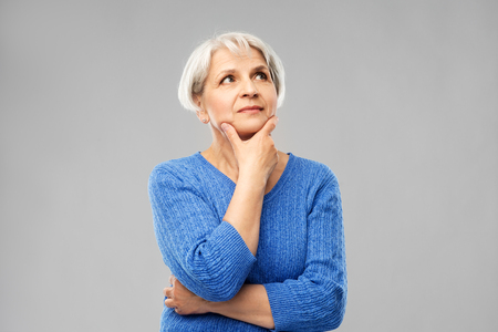 Foto de Old people and decision making concept - portrait of senior woman in blue sweater thinking over grey background - Imagen libre de derechos