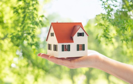 Photo for real estate, accommodation and eco friendly concept - close up of hand holding house or home model over green natural background - Royalty Free Image