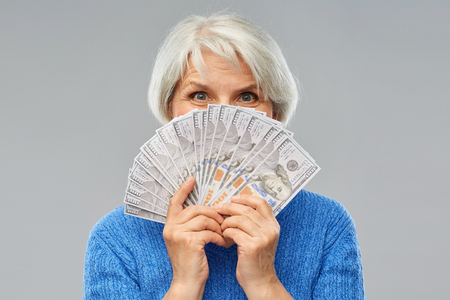 Foto de savings, finances and people concept - smiling senior woman hiding face behind hundreds of dollar money banknotes - Imagen libre de derechos