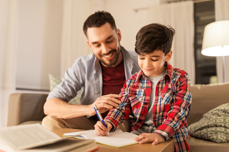 Photo pour Father and son doing homework together - image libre de droit