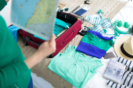 Foto de tourism, people and luggage concept - close up of young woman with map packing travel bag at home or hotel room - Imagen libre de derechos