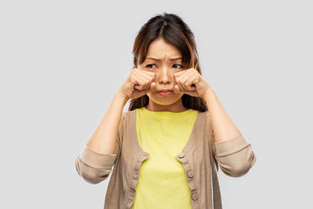 Foto de Sad Asian woman crying over grey background - Imagen libre de derechos