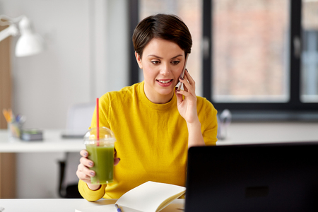 Photo pour woman with drink calling on smartphone at office - image libre de droit