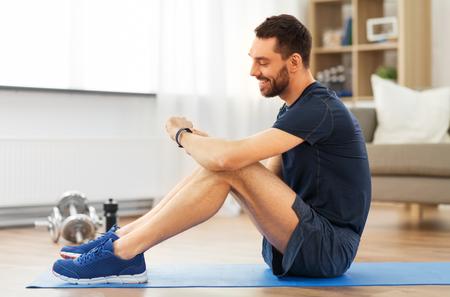 Foto de sport, technology and healthy lifestyle concept - smiling man with fitness tracker exercising at home - Imagen libre de derechos