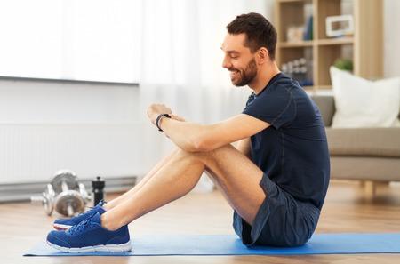 Foto de smiling man with fitness tracker exercising at home - Imagen libre de derechos