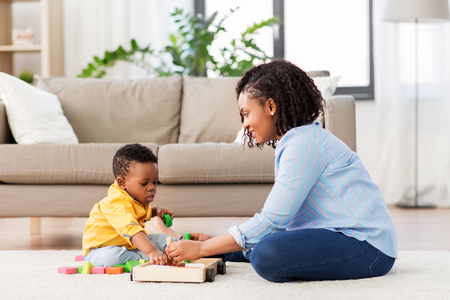 Photo pour mother and baby playing with toy blocks at home - image libre de droit