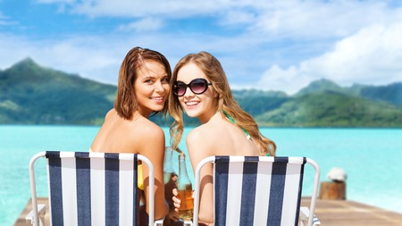 Foto de happy young women in bikini with drinks on beach - Imagen libre de derechos