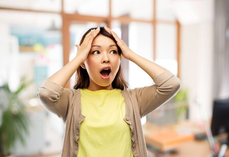 Foto de stressed asian woman holding to her head at office - Imagen libre de derechos