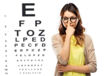 Foto de woman in glasses or student over eye test chart - Imagen libre de derechos