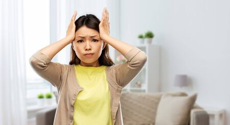 Foto de people, stress and despair concept - stressed asian woman holding to her head over home room background - Imagen libre de derechos