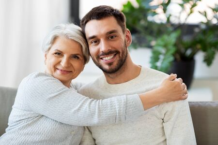 Photo pour Senior mother with adult son hugging at home - image libre de droit