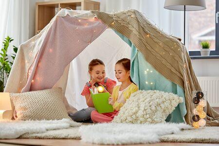 Foto de happy girls reading book in kids tent at home - Imagen libre de derechos