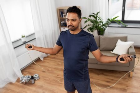 Photo for Indian man exercising with jump rope at home - Royalty Free Image