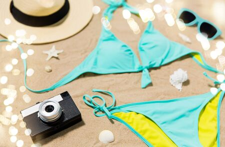 Photo for Vacation, travel and summer concept - bikini, hat, camera and sunglasses with seashells s on beach sand - Royalty Free Image