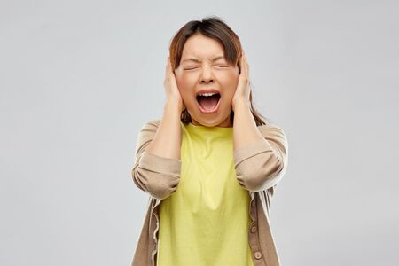 Foto de People, emotion and stress concept - Asian young woman closing ears by hands and screaming over grey background - Imagen libre de derechos